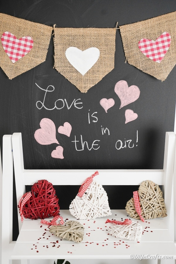 Burlap valentine banner on chalkboard above white shelf