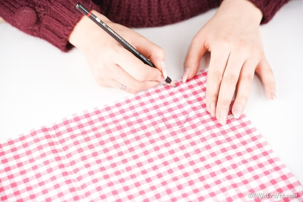 Tracing heart shape on red gingham fabric