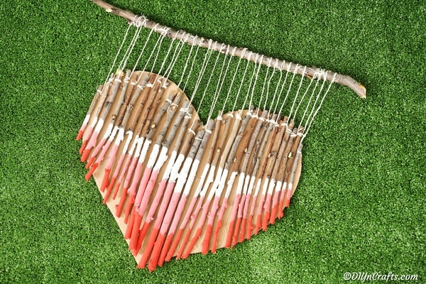 Painted red pink and white twig heart laying on grass