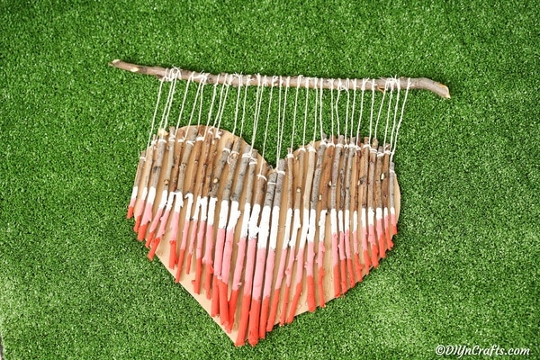 Wooden heart decoration on green grass