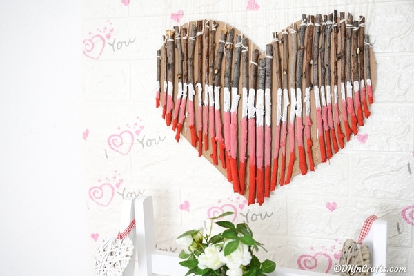 Wooden heart decoration hanging on wall with Valentine's Day decor
