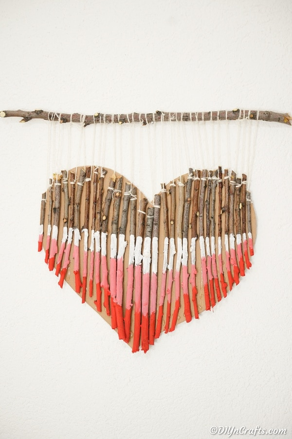 Painted twig wood heart wall art on white wall