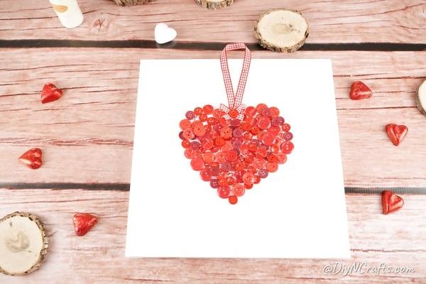 Button heart canvas art on wooden surface