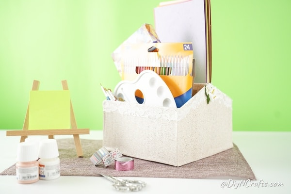 Cardboard organizer box filled with craft and school supplies