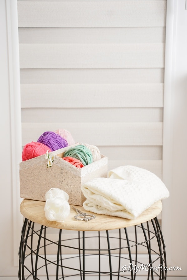 DIY organizer box filled with yarn on wood and wire table