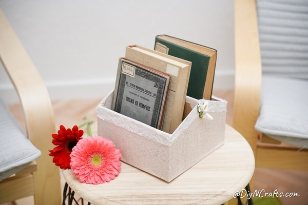 Books in a diy organizer on a wooden table