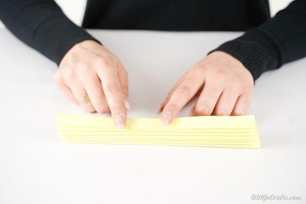 Folding yellow paper into a fan