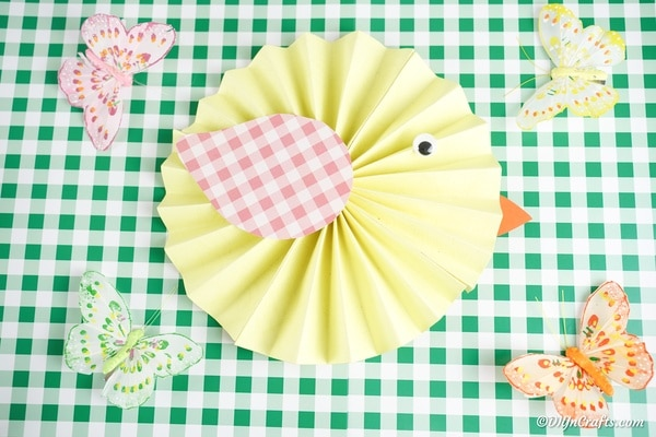 Paper chicken on a green checked surface