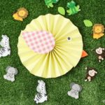 Paper bird kids craft on grass surrounded by mini toy animals