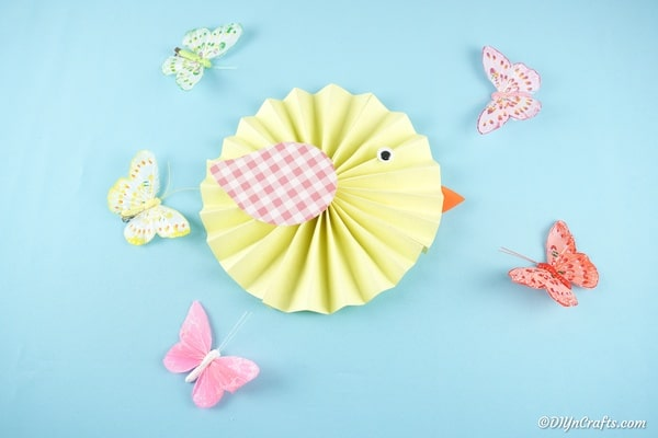 Paper chicken on blue surface surrounded by paper butterflies