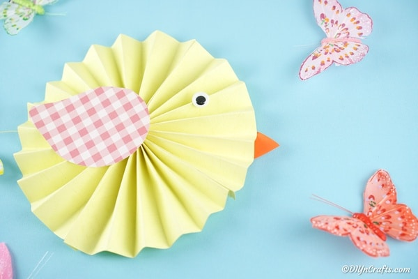 Yellow paper chick on blue paper with butterfly