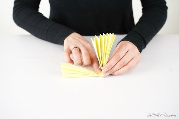 Folding folded paper in half to create a circle fan