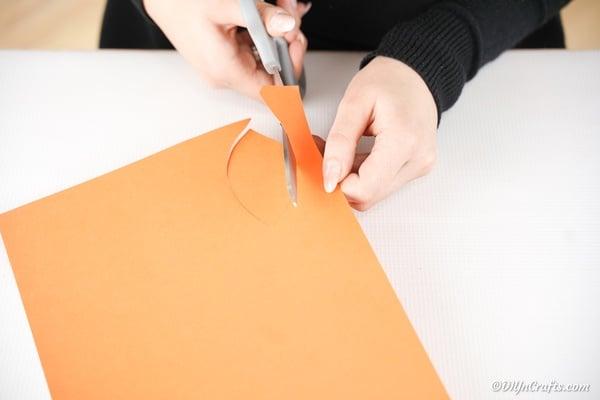 Cutting an orange beak from paper
