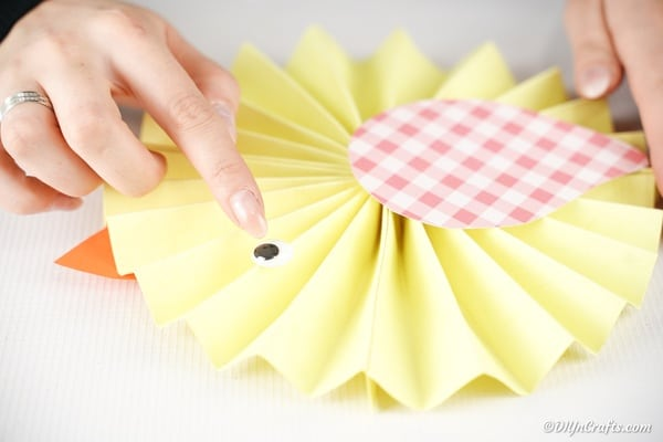 Gluing googly eye to paper fan chicken