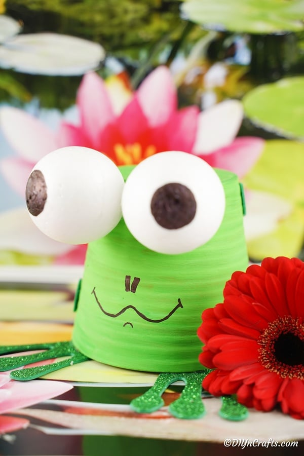 Flower pot garden frog on surface with fake flowers in red and pink