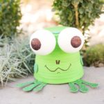 Flower pot garden frog sitting on a sidewalk