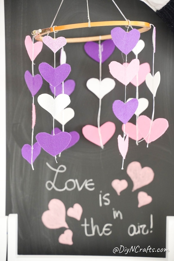 Heart mobile hanging in front of chalkboard