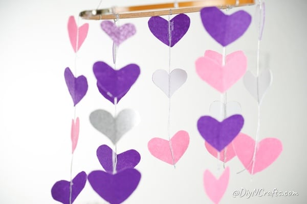 Heart mobile hanging against white wall