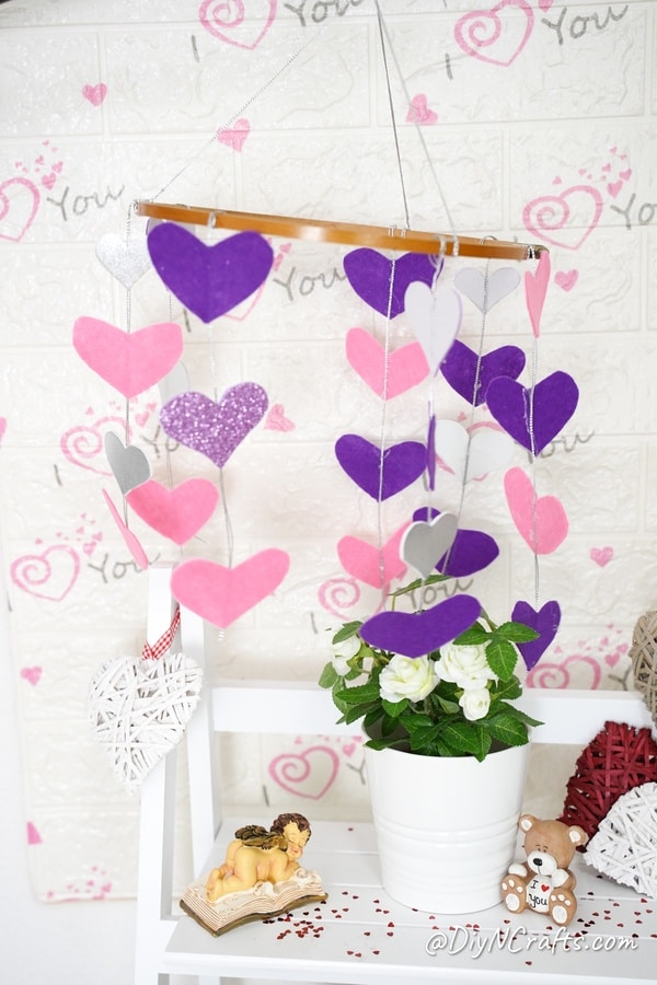 Paper hearts mobile hanging above white shelf