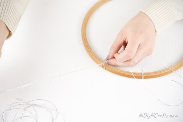 Tying twine onto embroidery hoop