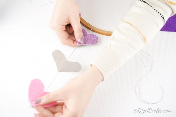 Gluing hearts into place on twine