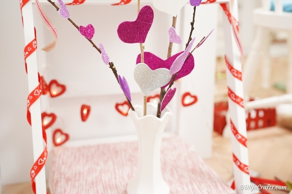 Bouquet of heart flowers on shelf with heart garland