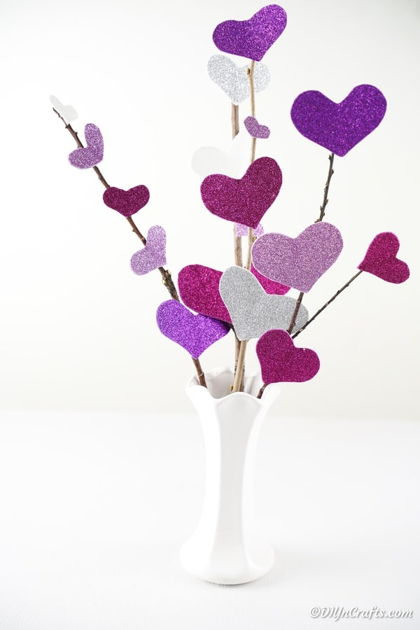 White vase filled with purple heart flower branches
