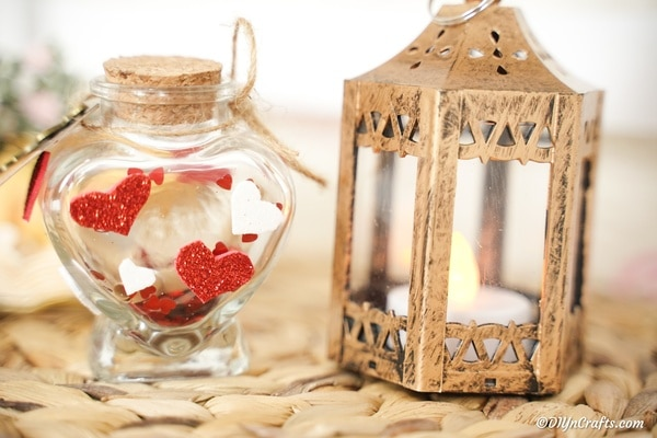 Valentine message in a bottle on woven mat next to lamp
