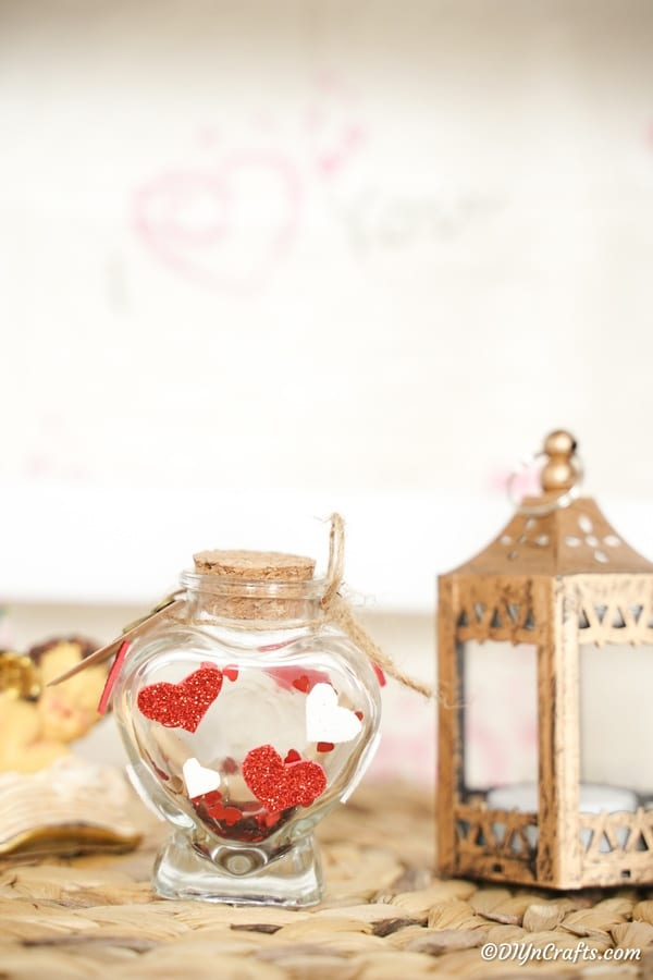 Valentine message in a bottle on table next to small lantern