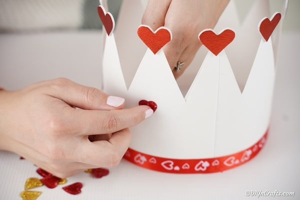 Attaching hearts to outside of paper crown