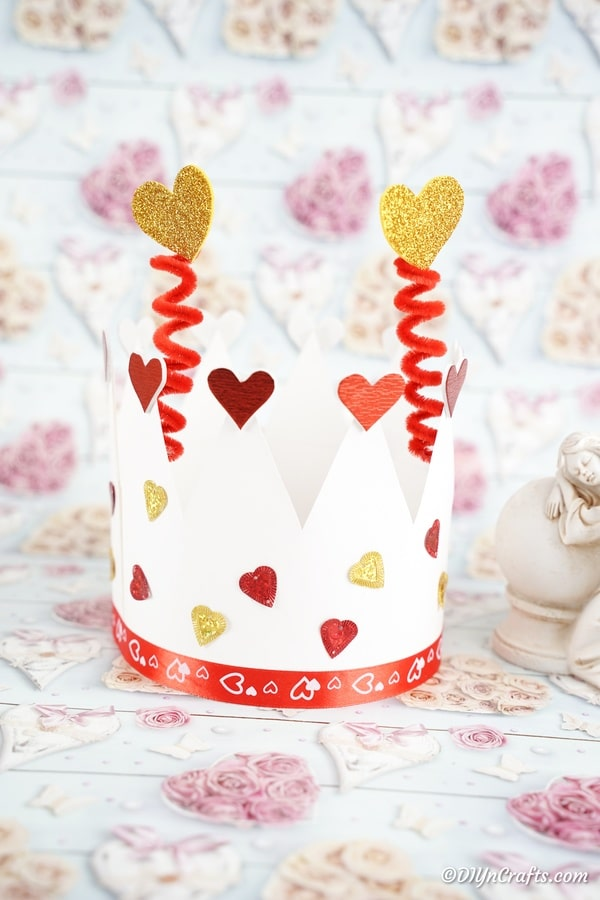 Paper crown sitting on Valentine's Day craft paper