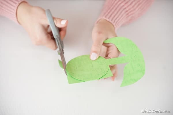 Cutting out the green flower shape from paper