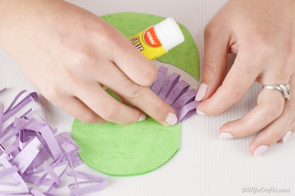 Gluing purple petals in place on paper flower