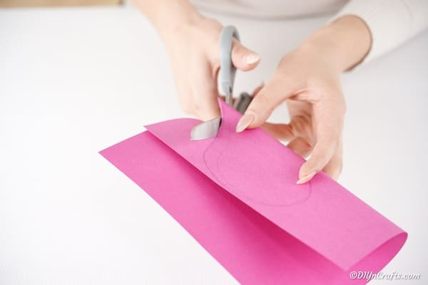 Cutting heart out of pink paper