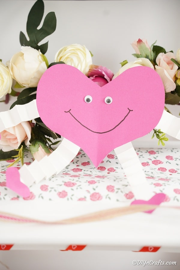Pink and white paper heart in front of white flowers