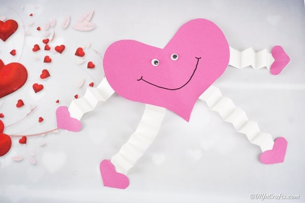 Pink paper heart on surface with heart decor