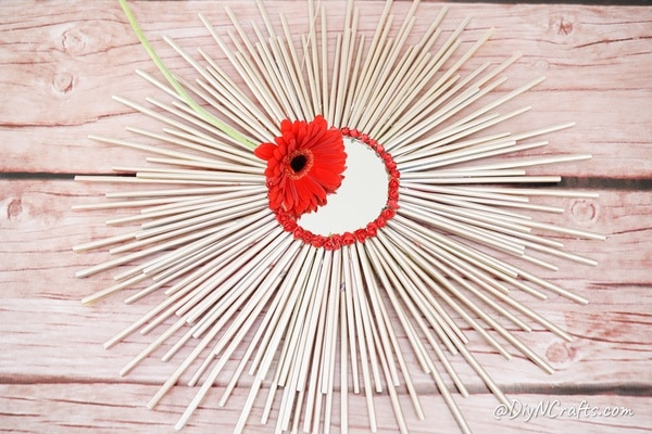 Paper straw mirror on wooden table