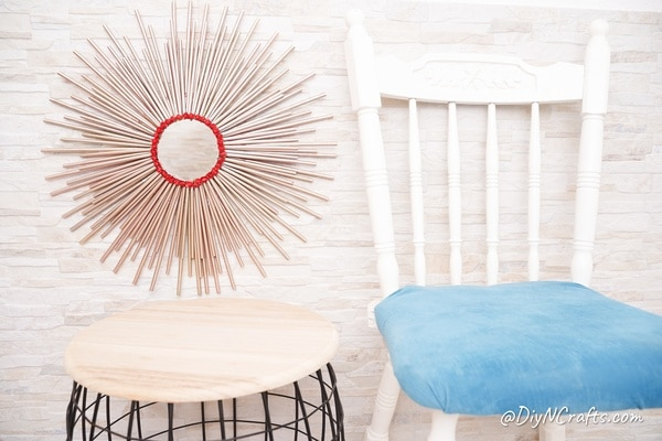 Paper straw mirror next to chair