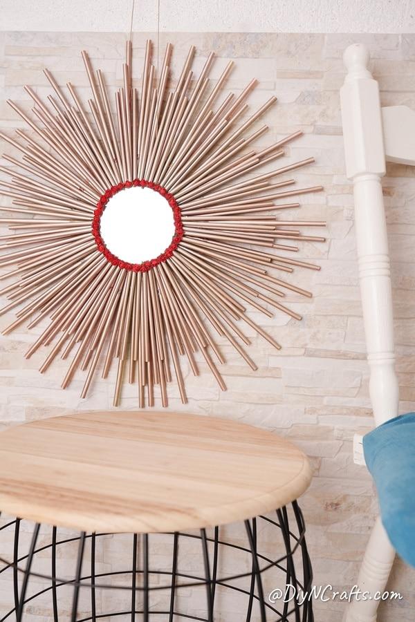 Paper straw mirror above wooden shelf