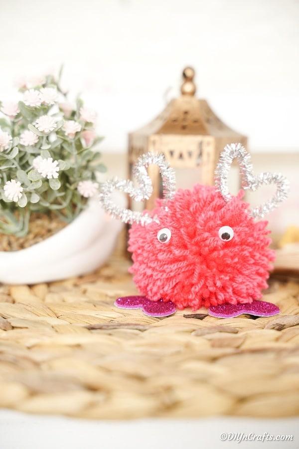 Valentine's day pom pom monster on woven mat