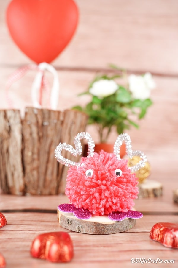 Valentine's day pom pom monster in front of wooden stump