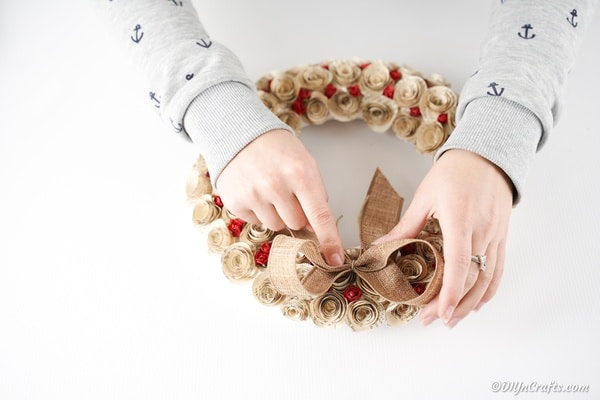 Attaching burlap bow to quilled rose wreath