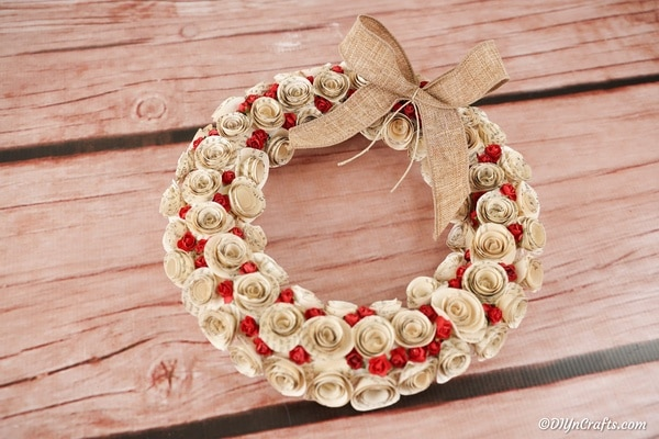 Quilled rose wreath on wooden surface