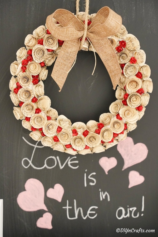 Rose wreath hanging in front of chalkboard
