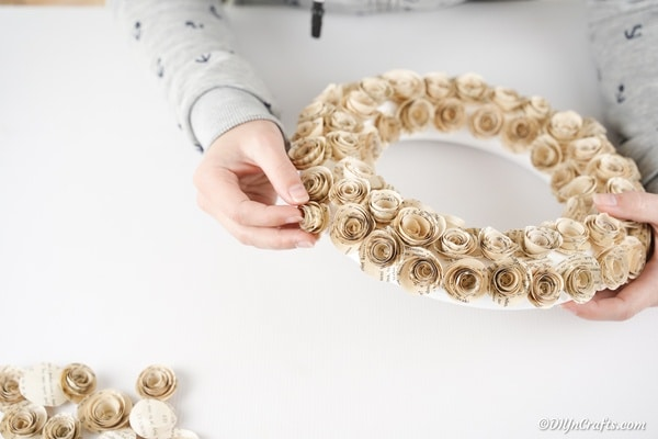 Adding paper roses to foam wreath form