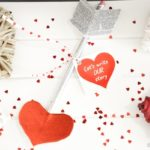 Valentine pencil on white paper with red confetti hearts