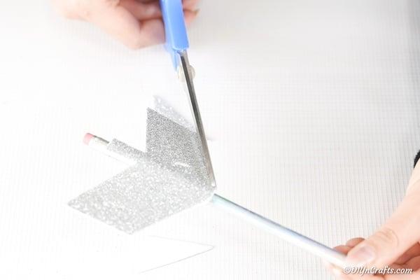 Trimming silver foam paper into arrow shape