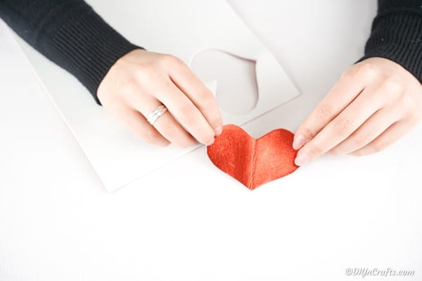 Cutting out a red heart from foam paper
