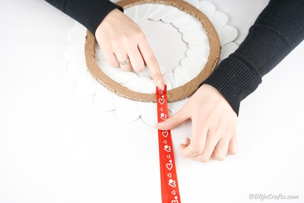 Gluing ribbon in place on heart wreath