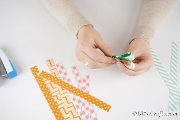 Folding green paper to create stme of carrot